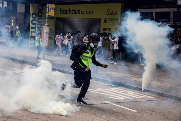 """当地时间5月24日下午,大批民众在铜锣湾发起""""反恶法大游行"""",警方则以水炮车和催泪瓦斯驱散示威人群,并且有百多人遭到拘捕。(法新社)"""