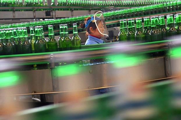 中国5月份制造业采购经理指数(PMI)延续了上个月的跌势,为50.6%。这一指数已经连续两个月下降,有分析指出,目前主要还是需求恢复缓慢,对生产造成了制约。图为工人在山东省淄博市一家啤酒厂的生产线上工作。(路透社)