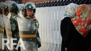 手持盾牌的武警在乌鲁木齐街头巡逻。(法新社)
