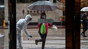 2020年3月29日,武汉一家酒店的员工全副武装给个人消毒。(法新社)