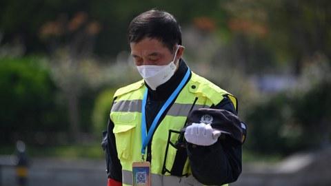 2020年4月4日,武汉的一名警察在脱帽向死于新冠病毒的人们致哀。(法新社)