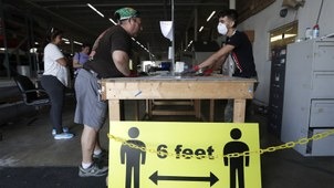 2020年3月27日,佛罗里达的一个工人带着口罩工作,前面是一个标志警示人们保持六英尺的距离。(美联社)