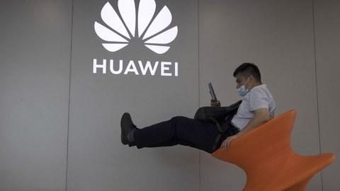 2020年7月31日,一名北京的男子戴着口罩坐在一个华为手机店门口。(美联社)