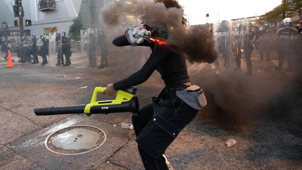 2020年6月2日,美国亚特兰大的 一名抗议者向警方投掷烟雾装置。(美联社)