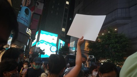 2020年6月30日晚上,港岛铜锣湾时代广场外一位少女手举一张白纸表示抗议。(Public Domain)