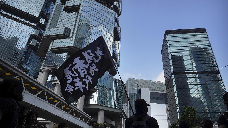 """2019年10月9日香港抗议者举着""""光复香港 时代革命""""的旗帜。(美联社)"""