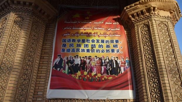 资料图片:2019年5月31日,在新疆和田地区一家集市上一张海报,推广讲普通话是民族团结的基础。(美联社)