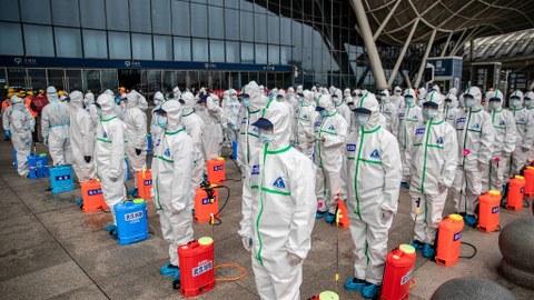 2020年3月24日,武汉火车站的工作人员正在准备喷洒清洁。(法新社)