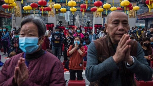 冠状病毒肆虐的大年初一,人们戴着口罩在佛庙祈祷。(法新社)
