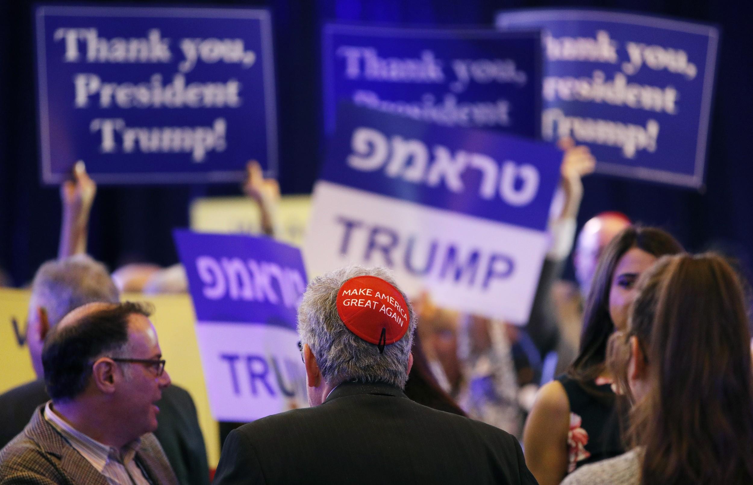 """一名男子头戴写有""""让美国再次伟大""""的圆顶小帽子参加一场支持特朗普总统的聚会。(美联社)"""
