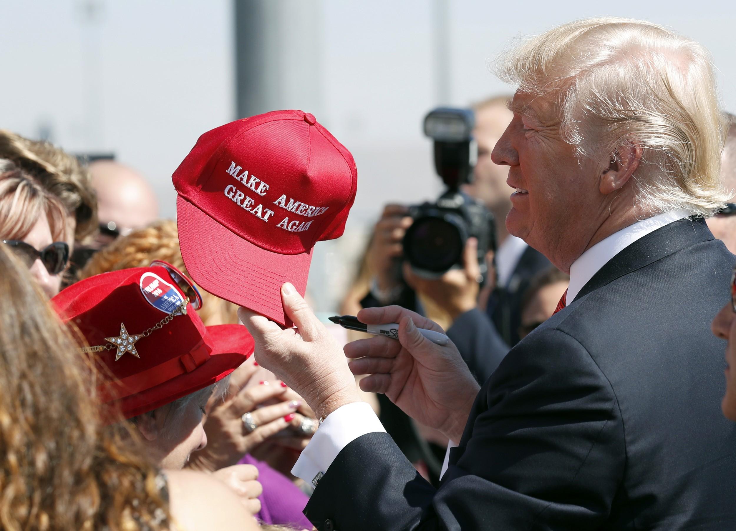 """美国总统特朗普拿着写有""""让美国再次伟大""""的帽子,签名后递给支持者。(美联社)"""