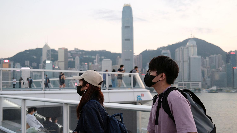 图为,2020年3月23日,戴着防护口罩的人走在香港天际线前。(路透社)