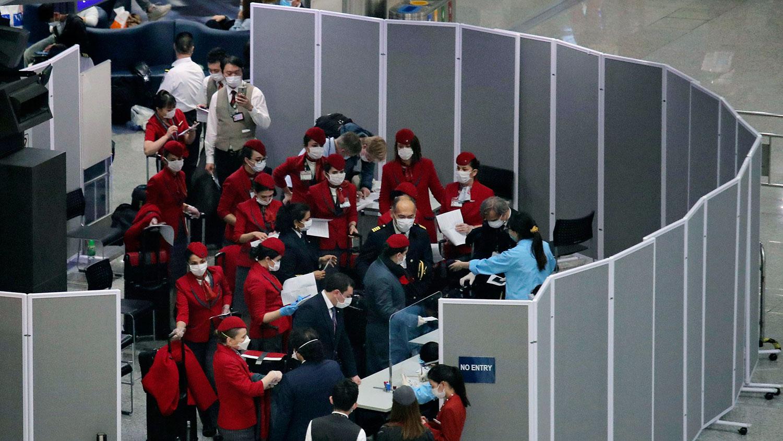 图为,2020年3月23日,戴着口罩的机组人员抵达香港机场。(美联社)
