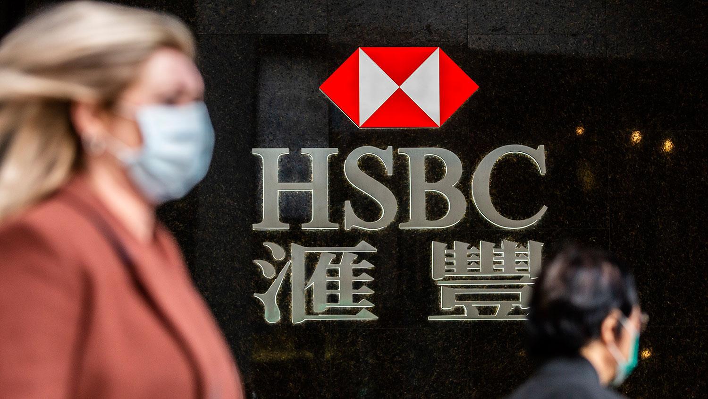 图为2020年2月18日,一名女士(左)走过香港汇丰银行标志。(法新社)