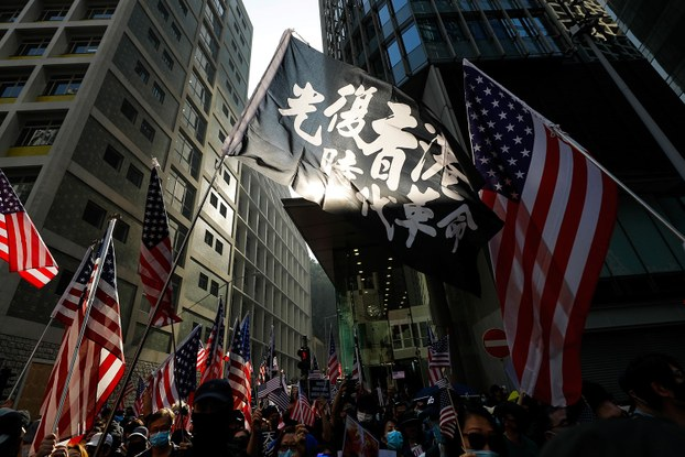 """资料图片:2019年12月1日,香港集会示威者举着""""光复香港 时代革命""""的旗帜。(美联社)"""