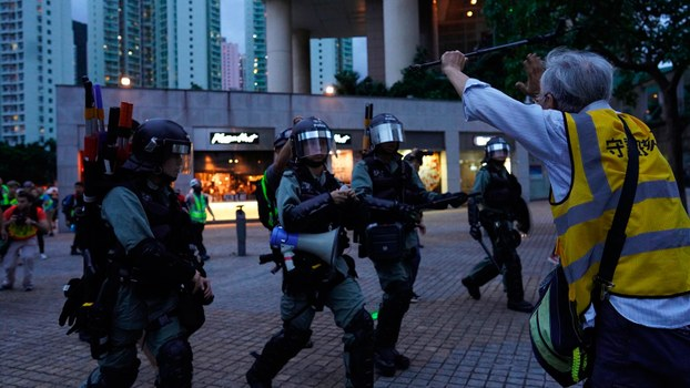 2019年9月1日,在香港东涌站外,一位老年人试图拦阻警察逮捕抗议者。(美联社)