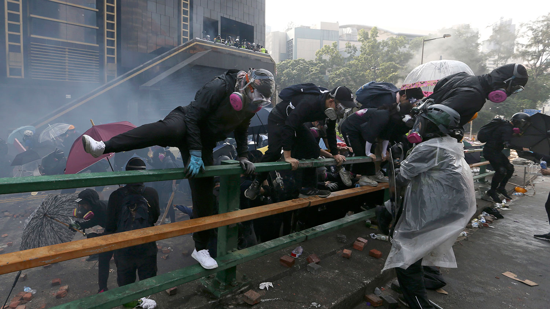 2019年11月18日,示威者在香港香港理工大学与警察发生冲突时爬上了栏杆。(美联社)