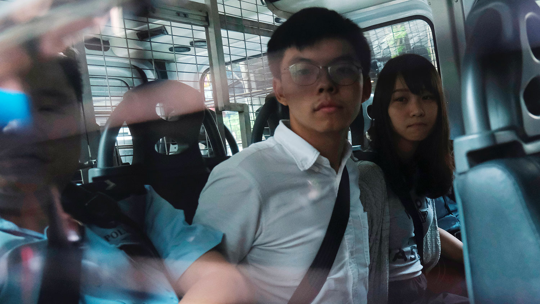 2019年8月30日,香港众志秘书长黄之锋(左)和成员周庭(右)早上被捕,下午由警车押往东区法院提堂。(路透社)