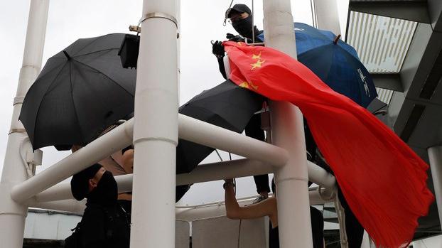 2019年8月3日,香港反送中运动一示威者,在尖沙咀天星码头将五星红旗解下。(美联社)