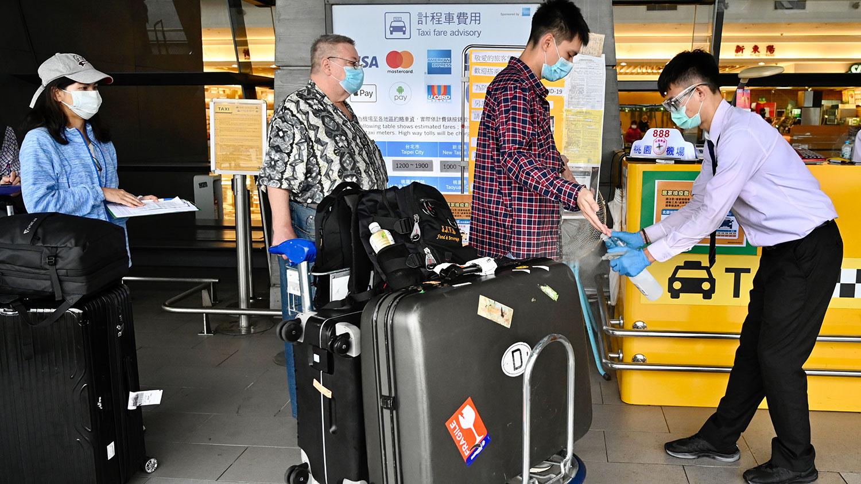 资料图片:2020年3月19日,到达台湾桃园机场的工作人员向乘客喷洒手部消毒剂。(法新社)