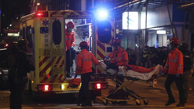 2020年1月27日,香港医护人员在旺角将一名抗议者送上救护车。(美联社)