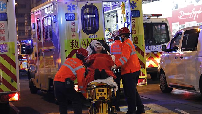2019年12月25日,香港医务工作者用担架将一名受伤的抗议者抬上救护车。(美联社)