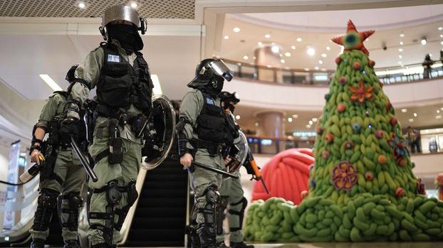 2019年12月24日,香港平安夜抗议集会期间,防暴警察在商场的圣诞树旁。(美联社)