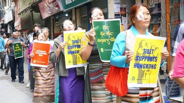 西藏妇女会8月31日在印度达兰萨拉举行遮右眼的游行,声援香港反送中行动。(西藏妇女会提供)