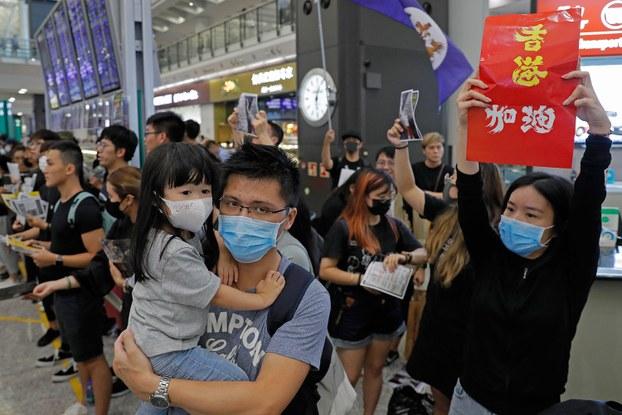 """2019年8月10日,香港反送中示威者在香港机场手举标语""""香港 加油""""。(美联社)"""