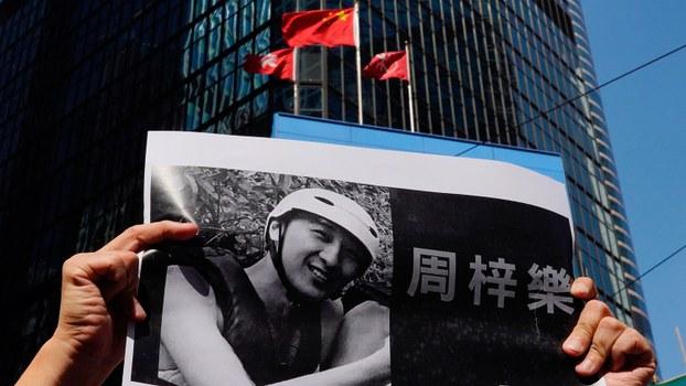 2019年11月4日,堕楼重伤的22岁的香港科技大学学生周梓乐在昏迷四天后不治身亡。图为11月8日,一名抗议者手中拿着周梓乐的照片。(美联社)