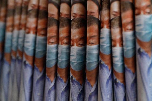 香港壹传媒创办人黎智英以及公司多位负责人本周一被警方拘捕,同日壹传媒股价飙升超過三倍,次日股价再升数倍。图为,2020年8月11日,在香港报摊上出售《苹果日报》报纸,头版以创办人黎智英被捕为头条。(AP)
