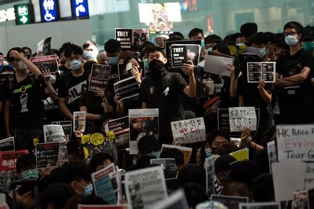 2019年8月13日,反送中示威者手持标语牌在香港国际机场。(法新社)