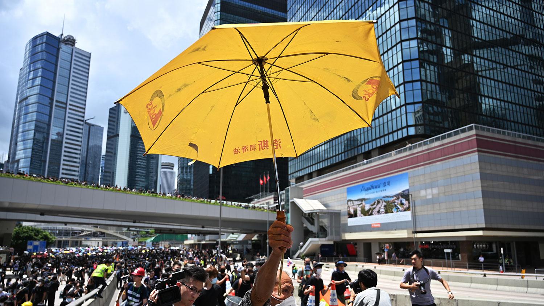 2019年6月21日,香港政府总部外,反送中示威者手举一把黄色雨伞。(法新社)