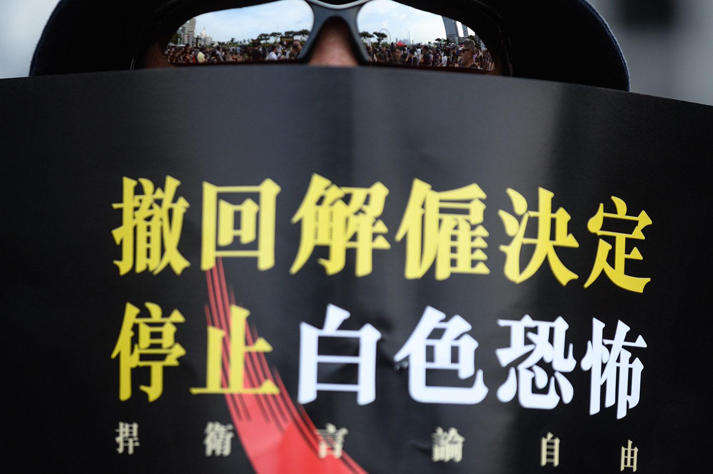 """2019年8月28日,国泰航空公司香港工作人员在一次集会手持标语牌""""撤回解雇决定 停止白色恐怖 捍卫言论自由""""。(法新社)"""