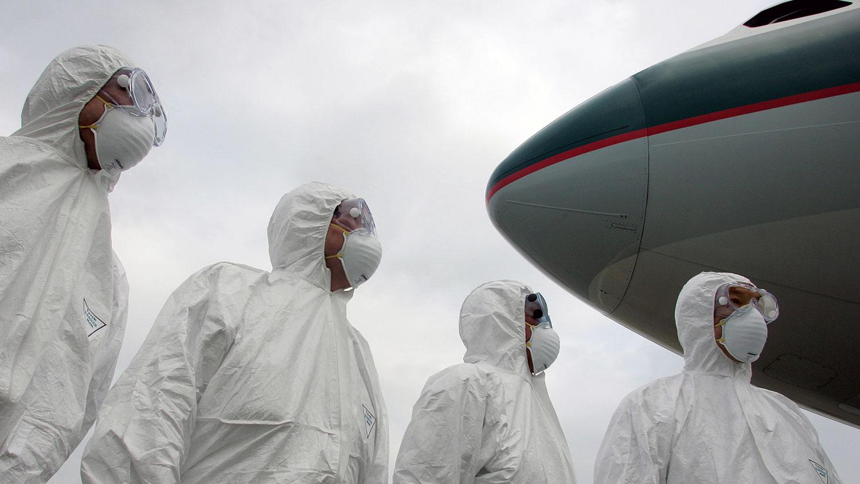 2020年1月1日,武汉的防疫工作显得异常紧张,在武汉机场的出发航班上,有全副保护衣人员上机检疫。(资料图/法新社)