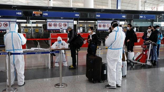 资料图片:2020年3月16日,身穿防护服的工作人员在北京首都国际机场的登机柜台前对乘客进行登记。(路透社)