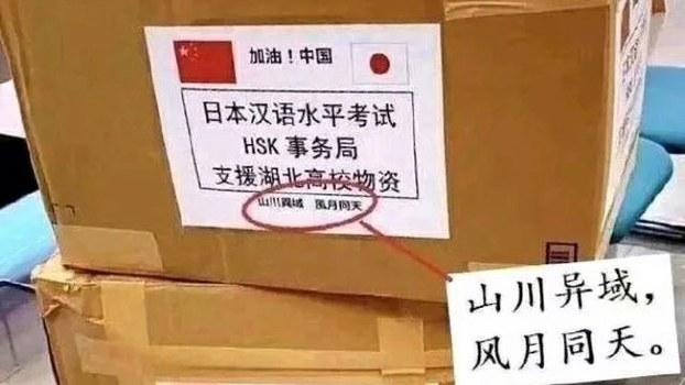 """日本汉语水平考试事务所捐赠给湖北大批口罩和红外体温计,物资外包装的标签上写着八个字:""""山川异域,风月同天""""。(Public Domain)"""