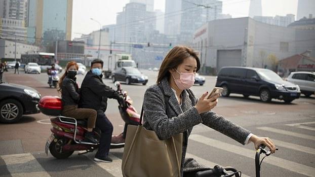 2020年3月30日北京街头戴口罩的民众。中国专家钟南山称,全球疫情将在4月底出现拐点,而中国不会有第二波疫情高峰。(美联社)