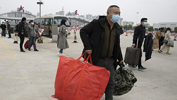 2020年4月2日戴着口罩从外地返回新冠病毒最早爆发地武汉的居民(美联社)