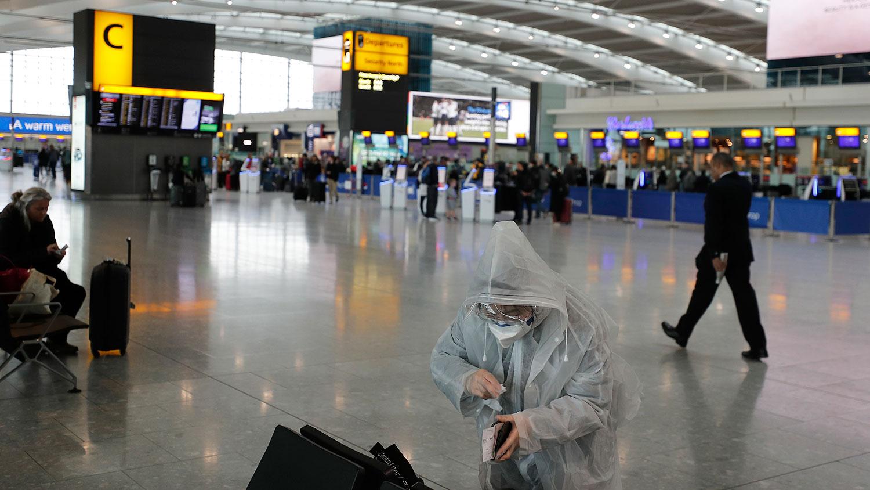 图为:2020年3月18,旅行者在英国伦敦希思罗机场。(美联社)