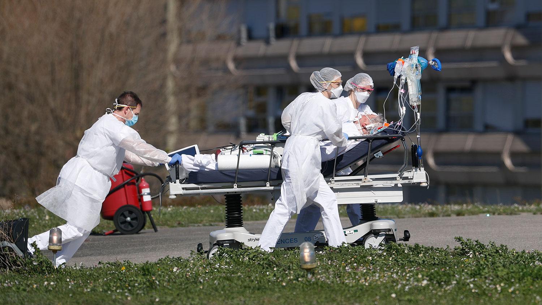 图为,2020年3月23日,法国米卢斯市民医院医生推着新冠肺炎重症患者。(美联社)