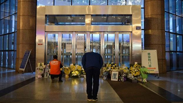 2020年2月7日,湖北省武汉市武汉市中心医院后湖分院外,一名武汉市民在已故的眼科医生李文亮的照片前鞠躬。(法新社)