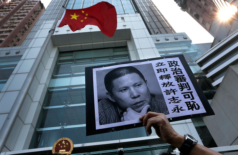 图为一名示威者在香港中联办声援许志永。(美联社)
