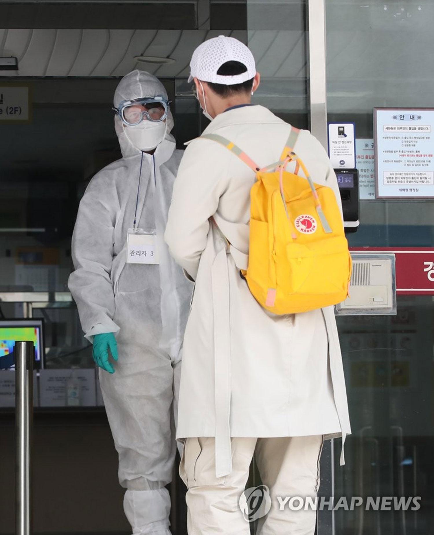 2020年2月24日,在位于首尔东大门区的庆熙大学,一名返校的中国留学生在身穿防护服的工作人员的引导下进入宿舍。 (韩联社)