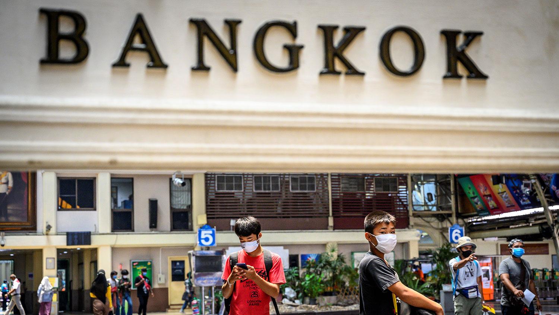 图为,2020年3月31日,戴着口罩的旅客在泰国曼谷中央火车站等车。(法新社)