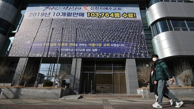 一名男子戴着口罩走过韩国新天地教会前。(法新社)