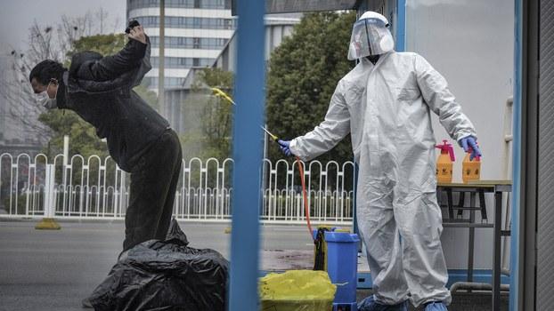 一名武汉男子在离开一座武汉的医院时接受工作人员消毒。(法新社)