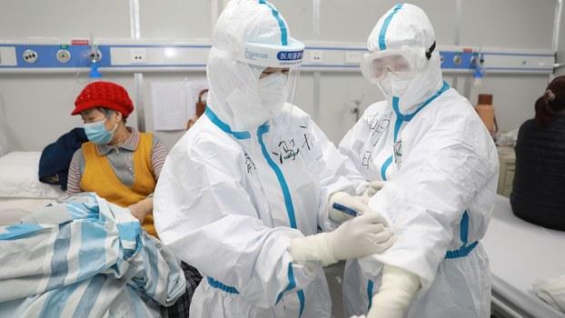 2020年2月16日,湖北省武汉市,医务工作者在雷神山医院(一家临时医院治疗新型冠状病毒患者)同事的防护服垫着写下患者的饮食信息。(路透社)