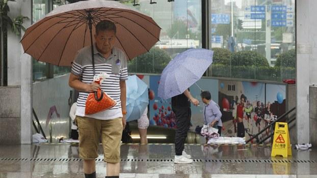 中国南方连续降雨,图为上海居民在雨中出行。(美联社)