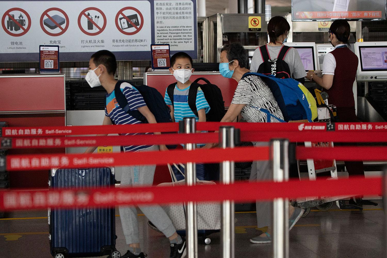 2020年6月17日,戴着口罩的乘客在北京首都机场3号航站楼办理登机手续。(美联社)